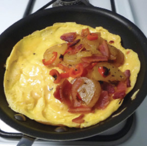 American_omelet_add_filling_when_eggs_are_cooked_but_moist
