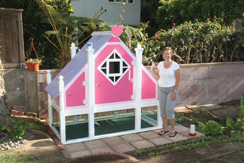 "Paulina Shahin stands in front of the ""Barbie Dream House"" coop that her husband, Samir, designed and built for their flock of chickens. Most of the finishing touches are completed, including the wire mesh for the run under the house."