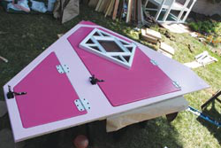 The front door has the stained-glass window installed. The gate latches were put on. The hinges were pilot drilled and screwed in, then removed before the doors were cut to keep the hinges perfectly aligned during assembly. The doors were painted a contrasting color from the rest of the frame.