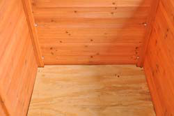 The original slat floor was replaced with 1/2-inch plywood to reduce drafts, hold bedding, and provide security against predators.